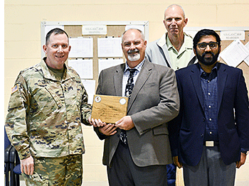Mike Springman, Joe Pickowitz, and Shantanu Pai on the right posing for photo with Army representative and the award