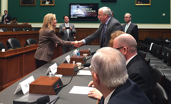 Walt Magnussen shaking hands with a member of the house of representatives.