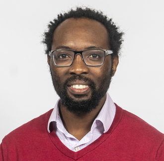 Lloyd Munjanja in glasses, a collared shirt and red sweater on a white background