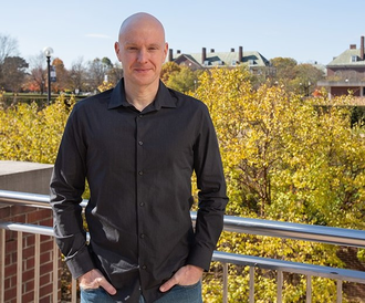 Photo of Doug Mitchell standing on an outdoor balcony overlooking U of I campus