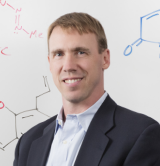Head shot Professor Paul Hergenrother in front of a white wipe-off board with chemistry illustrations