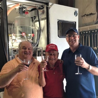 Photo of Greg George, Ben Mozier and Ricky Ford holding wine glasses in front of the distilled spirit technology they developed