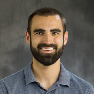 Head shot of graduate student Matthew Boudreau on a dark gray background