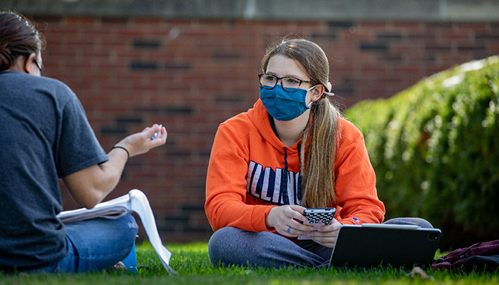 students having a conversation outside wearing masks