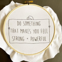 "Embroidered image with black thread on white fabric: a sign that says ""Do something that makes you feel strong + powerful"" with the top of a person's head peeking out from the top and their hands holding it on the sides"