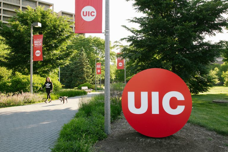 A person with a dog walking through UIC campus near the UIC button sign