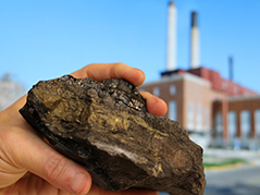 hand holding piece of coal with a power plant in the background